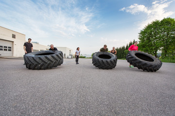Fitness team flipping heavy tires outdoor