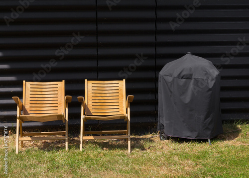 Two chairs and a covered grill