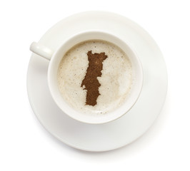Cup of coffee with foam and powder in the shape of Portugal.(ser