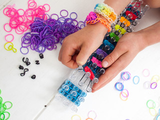 childs hands making a multicoloured elastic band bracelet on a b