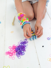 kneeling childs hands making a multicoloured elastic band bracel