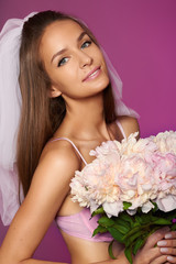 Beautiful bride in pink lace lingerie with bouquet of peonies