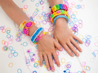 arms of a child wearing multicoloured bracelets