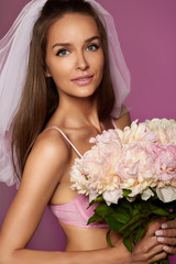 Pretty fiancee in veil pink lingerie with bouquet of peonies