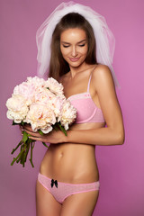 Sexy bride in veil lace lingerie with bouquet of peonies