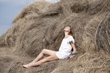 Young beautiful woman in the hayloft in the village