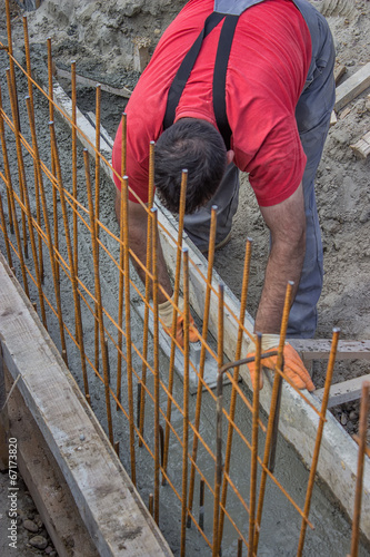 Construction worker smooth fresh concrete with trowel in a ditch