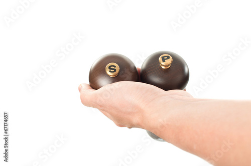 Asian male hand holding wooden salt and pepper shakers on white