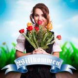 attraktive junge Frau im Dirndl mit Tulpen und Willkommensgruß