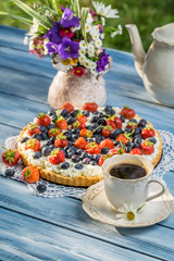 Fruit tart served with coffee in the summer garden