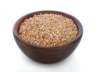 Ripe wheat in a wooden bowl on the old rustic table