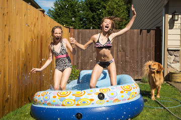 Kids jumping in an inflatable pool