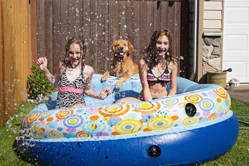 Kids and a dog splashing in a pool