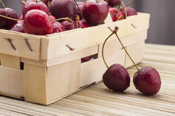 cherries in a basket on a bamboo mat