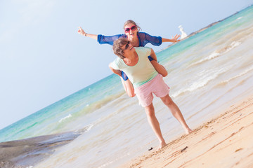 Man giving piggyback ride to girlfriend by the ocean