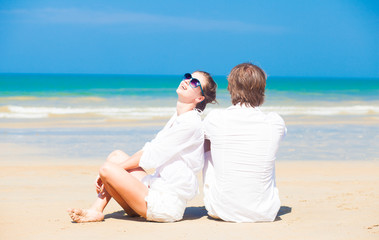 young couple in white sitting at tropical beach