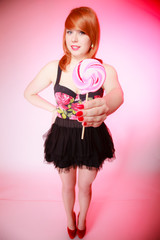 Sexy young woman showing candy. Redhair girl
