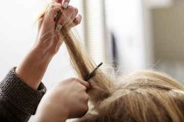 Hairstylist combing female client blond girl