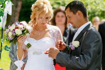 beautiful young wedding couple exchange wedding rings