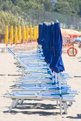 Row of closed beach umbrellas and sun beds