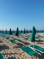 deckchairs and sun umbrellas on a mediterranean beach