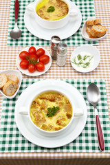Tasty soup in saucepans on tablecloth, close up