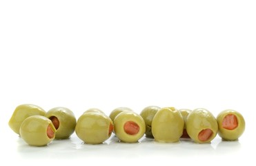 A row of green olives on a white background with copy space