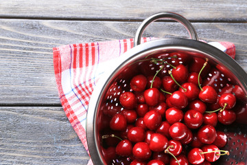 Sweet cherries in colander on color wooden background