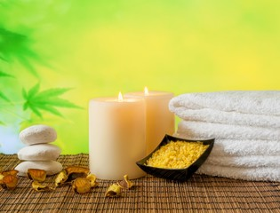 Spa massage with towel stacked, candles and sea salt