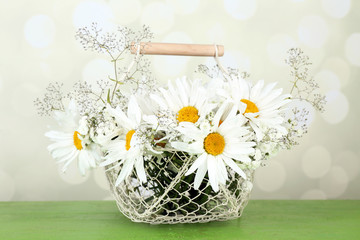 Beautiful chamomiles in basket on table on bright background