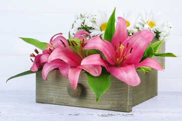 Beautiful flowers in crate on wooden background