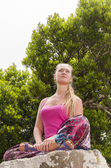 Young woman practicing yoga on the nature