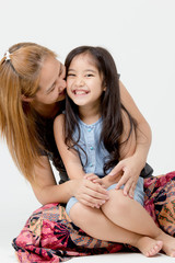 Portrait of happy Asian daughter kissed by mother