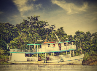 Wooden boat on the Amazon river, Brazil, vintage retro instagram