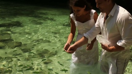 Couple in love stands crystal clear water with fish
