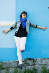Beautiful positive woman posing in front of a blue wall