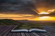 Stunning vibrant Summer sunset over escarpemt landscape Creative