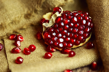 Raw pomegranate with seeds on sacking