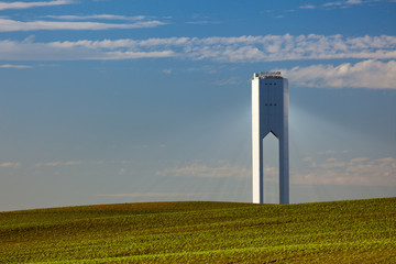 Solar Tower with rays  - thermo-solar power - blue sky and green