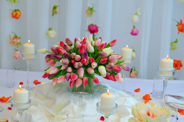 festive table decorated with a bouquet of tulips, candles