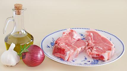 côtelles de veau crues dans assiette avec flacon d'huile olive