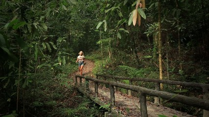 Girl walking near the creek in the jungle