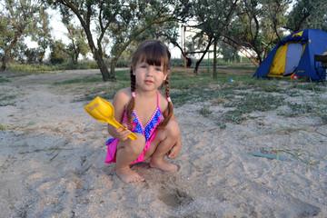 Девочка на пляже с лопаткой