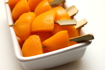 peach fruits on skewers in white cup