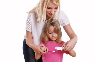 Mutter zeigt ihrem Kind wie man Zähne putzt