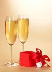 Two wine glasses with champagne and gift