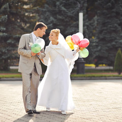 Young newlywed couple with balloons.