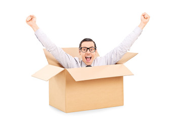 Young man gesturing happiness deep inside a box