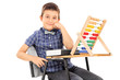 Schoolboy sitting at a desk with an abacus on it