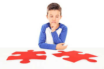 Pensive boy looking at two pieces of puzzle
